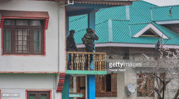 Indian army troopers look towards a residential house where suspected rebels are trapped during a gun battle between Indian government forces and...