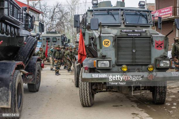 Indian army troopers stand guard near the site of gun battle between Indian government forces and suspected rebels during a gun battle between Indian...