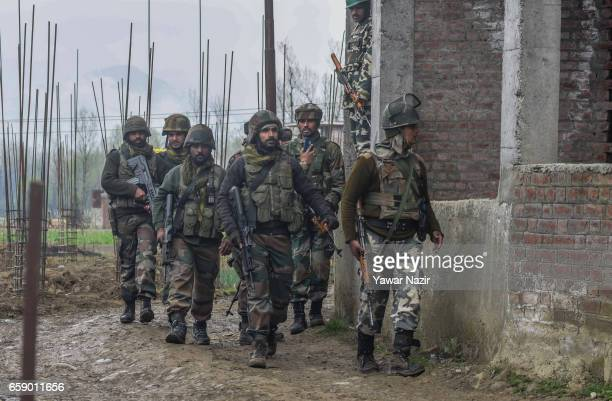 Indian army troopers walk towards gun battle site during a gun battle between forces and suspected rebels on March 28 2017 in Chadoora 17 Kilometer...