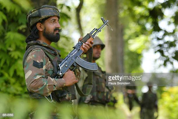 Indian Army troops stand guard along the road that leads to the Line of Control June 10 2002 outside Srinagar Kashmir India The troops are on duty...