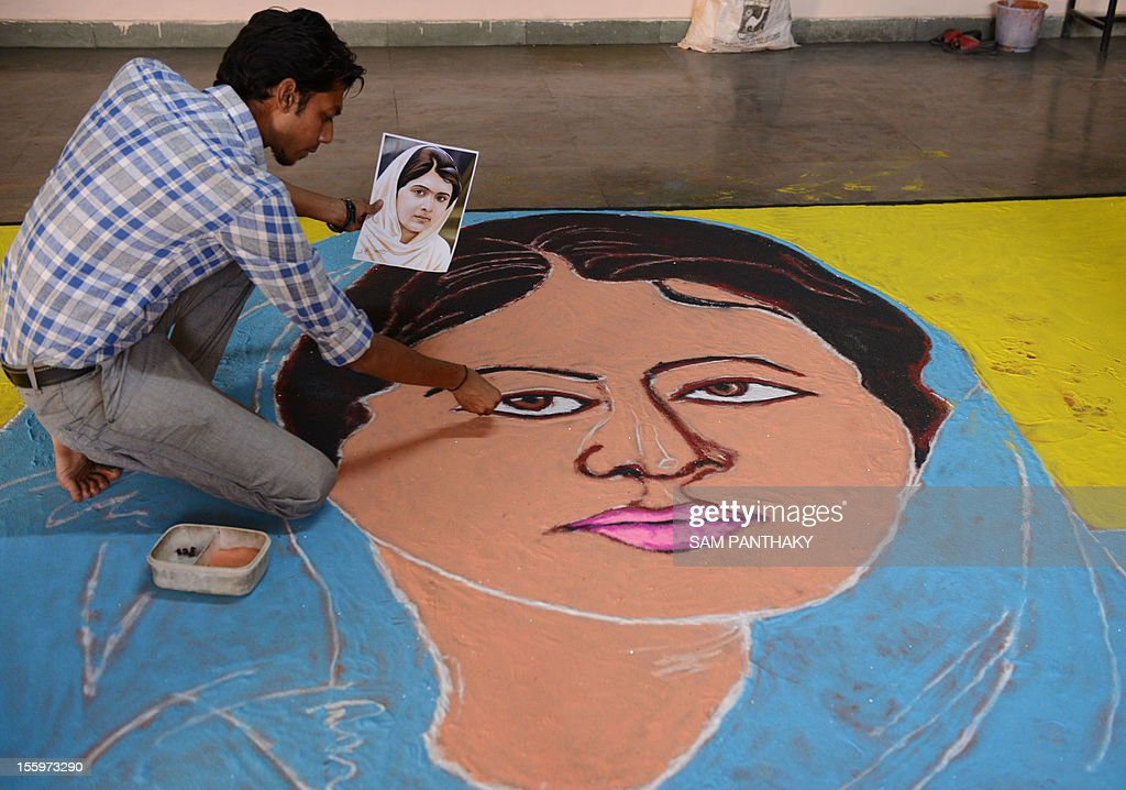 Indian art teacher, Ashish Jadav gives the finishing touches to a 'Malala Rangoli' at H B Kapadia New High School in Ahmedabad on November 10, 2012. World Malala Day is being observed today to honour Pakistani child activist Malala Yousafzai who was shot by Taliban gunmen. In his message, UN Secretary General Ban Ki-moon has called on the international community to join the UN campaign to put education first for Malala and girls and boys throughout the world. AFP PHOTO / Sam PANTHAKY
