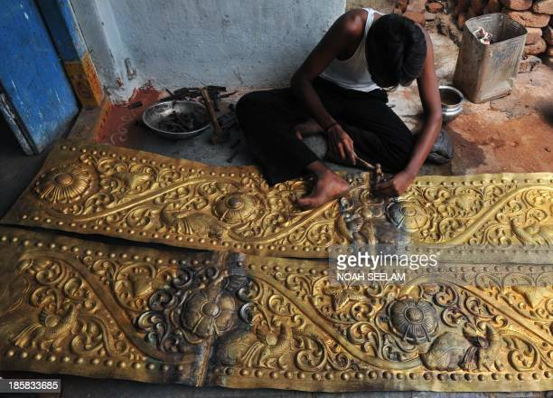 Indian artisan Aadimulam Rakesh embosses designs onto a brass sheet destined to decorate a Hindu temple in Hyderabad on May 8 2010 Sculptural art on...