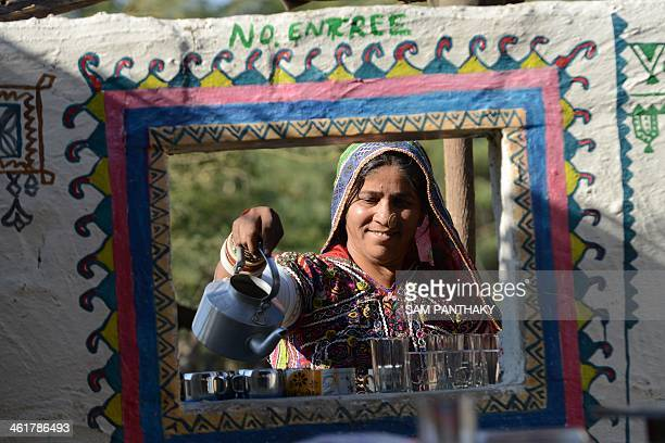 Indian artisan Bayabai Umra wears traditional embroidered dress as she pours tea at Hodka village some 470 kms from Ahmedabad in the Kutch district...