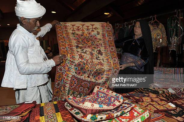Indian artisans Bechar Devsinh Rabari and Devalben from Gujarat's remote Kutch region display their creations of handpainted bedsheets on the opening...