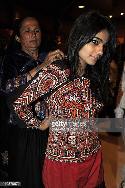 Indian artisans Devalben from Gujarat's remote Kutch region assists a young woman as she tries on a creation during the opening day of 'Craftroots...