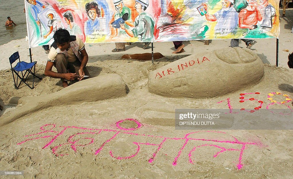 Indian artist Rajkapor (C) makes a sand sculpture representing the Air India Express Boeing 737-800 in Allahabad on May 24, 2010. Investigators combed the wreckage of an Air India Express jet that crashed into a forested gorge with the loss of 158 lives, searching for the 'black box' data recorder. AFP PHOTO/Diptendu DUTTA