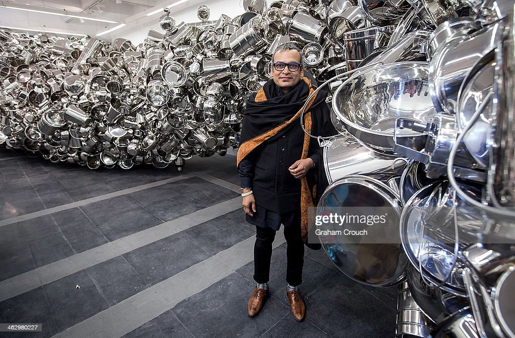 Indian artist Subodh Gupta in front of the sculpture ' Thosa pani ' that is part of Gupta's first major museum show in New Delhi, 'Everything Is Inside' at National Gallery of Modern Art on January 16, 2014 in New Delhi, India.. The exhibition traces Gupta's career from his upbringing in the rural province of Bihar to his rise to prominence as one of India's foremost contemporary artists.The show draws together his varied body of work including painting sculpture, video and