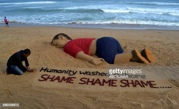 Indian artist Sudarsan Pattnaik works on a sand sculpture depicting drowned Syrian boy Aylan Kurdi at Puri beach some 65 kilometers away from...