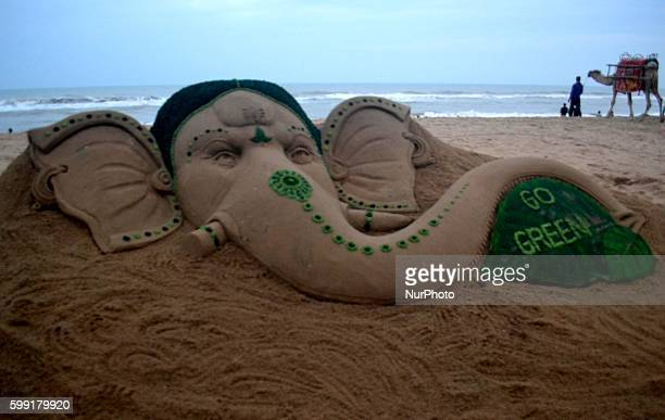 Indian artist Sudarshan Pattnaik creates a sand sculpture to spread an awareness message through elephant headed God Ganesh ahead of Ganesh chatruthi...