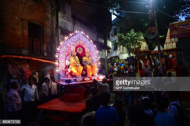 TOPSHOT Indian artists dressed as Hindu god Rama and his companion Laxman sit in a tableau passing through a narrow street during a Dussehra festival...