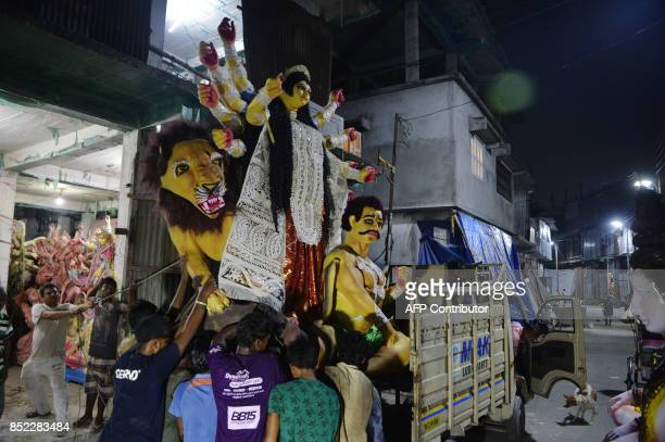 Indian artists move a clay statue of Hindu goddess Durga at a workshop in Siliguri on September 23 2017 The fiveday Durga Puja festival commemorates...