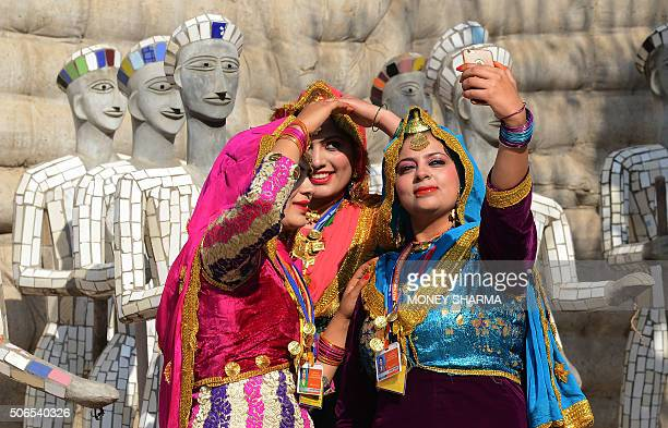 Indian artists take a selfie as they wait for the arrival of Indian Prime Minister Narendra Modi and French President Francois Hollande at the Rock...