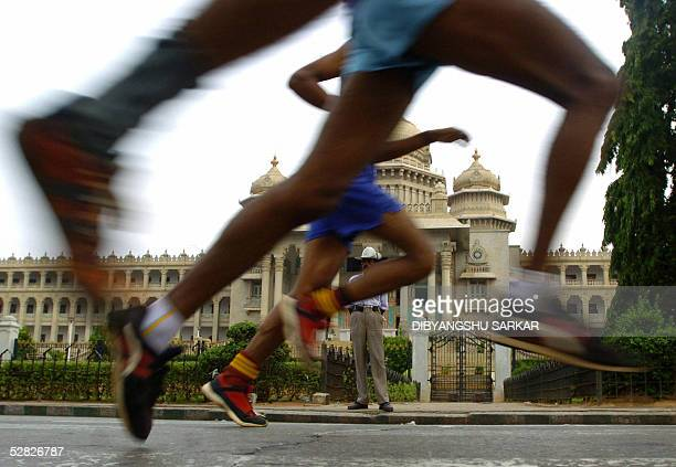 Indian athletes run past the Bidhan Saudha Building as they take part in the first Bangalore International Marathon in Bangalore 15 May 2005 With...