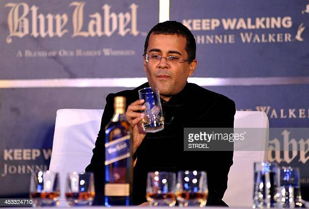 Indian author and screenwriter Chetan Bhagat drinks during a promotional event in Mumbai late August 7 2014 AFP PHOTO/STR