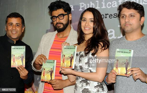 Indian author columnist and screenwriter Chetan Bhagat Bollywood actors Arjun Kapoor and Shraddha Kapoor pose for a photograph during a promotional...