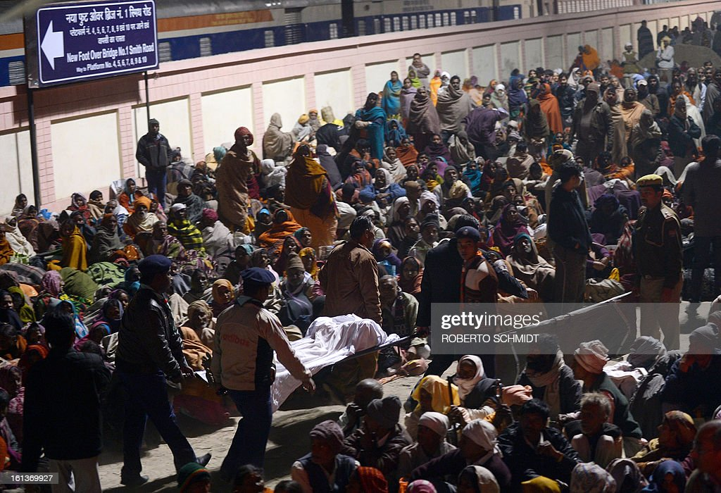 Indian authorities carry the bodies of two travellers killed in a stampede at the railway station in Allahabad on February 10, 2013. At least 10 people died in the stampede as pilgrims headed home from India's giant Kumbh Mela festival, which drew a record 30 million people to the banks of the river Ganges. Dozens more were injured in the crush and some local television channels put the death toll as high as 20. Local officials said that the railings on a bridge at Allahabad station had given way under the pressure of the mass of people, while eyewitnesses told local media that the police had baton-charged the crowd leading to panic. AFP PHOTO/ ROBERTO SCHMIDT