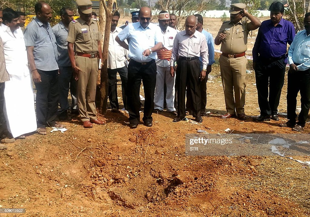 Indian authorities inspect the site of a suspected meteorite landing on February 7 2016 in Vellore district in southern Tamil Nadu state in an impact...