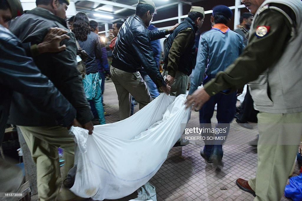 Indian authorities remove the body of one of the travellers that were killed during a stampede at the railway station in Allahabad on February 10, 2013. At least 10 people died in the stampede as pilgrims headed home from India's giant Kumbh Mela festival, which drew a record 30 million people to the banks of the river Ganges. The lives were lost at the main railway station where 10 corpses wrapped in white sheets could be seen on a train platform several hours after the incident which occurred in the early evening, an AFP photographer said.