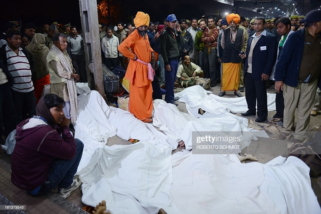 Indian authorities stand among some of the travellers that were killed during a stampede at the railway station in Allahabad, on February 10, 2013. At least 10 people died in the stampede as pilgrims headed home from India's giant Kumbh Mela festival, which drew a record 30 million people to the banks of the river Ganges. The lives were lost at the main railway station where 10 corpses wrapped in white sheets could be seen on a train platform several hours after the incident which occurred in the early evening, an AFP photographer said.