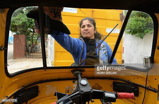 Indian auto rickshaw driver Vennapusa Narayanamma cleans the windshield of her auto rickshaw outside her home in the Nijampet District on the...