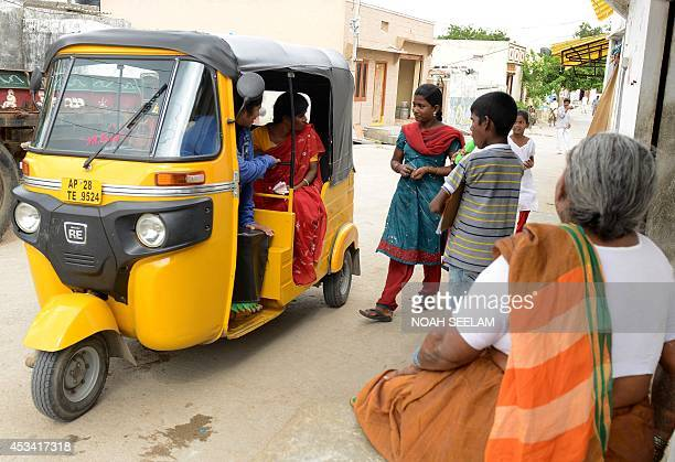 Indian auto rickshaw driver Vennapusa Narayanamma greets passengers as they board her vehicle in the Nijampet District on the outskirts of Hyderabad...