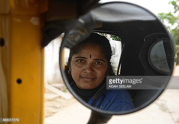 Indian auto rickshaw driver Vennapusa Narayanamma poses in her vehicle as she waits for passengers in the Bachupally District on the outskirts of...