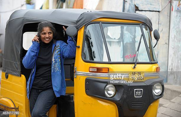 Indian auto rickshaw driver Vennapusa Narayanamma speaks on her cellular telephone as she waits for passenegrs in Bachupally District on the...