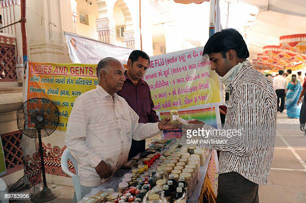 Indian ayurvedic doctor Amratlal Soni and son Harshad interact with a prospective customer as they sell ayurvedic medicines from a stall at The...
