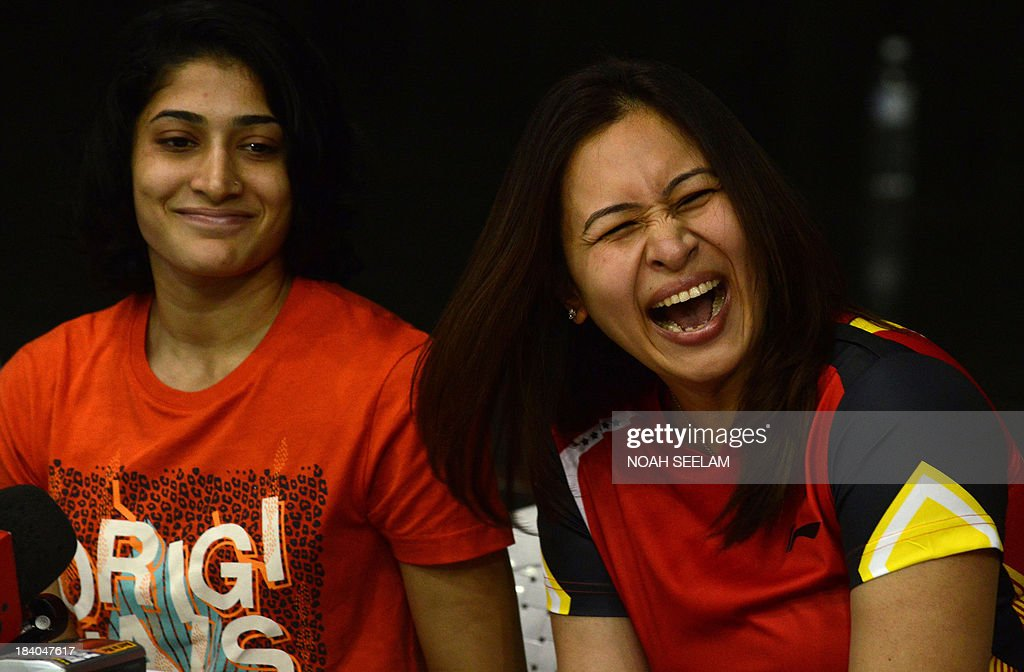Indian badminton player Jwala Gutta (R) gestures, as badminton partner Ashwini Ponnappa looks on during a press conference in Hyderabad on October 11, 2013. The Badminton Association India (BAI) disciplinary committee recommended a life ban on Gutta for trying to stop some players of her franchise, Krrish Delhi Smashers, from playing a match against Banga Beats in the Indian Badminton League in August. The Delhi High Court passed a stay-order against a life-ban on Jwala Gutta, however the BAI withdrew Gutta and her doubles partner, Ashwini Ponnappa from the Denmark Open. AFP PHOTO / Noah SEELAM