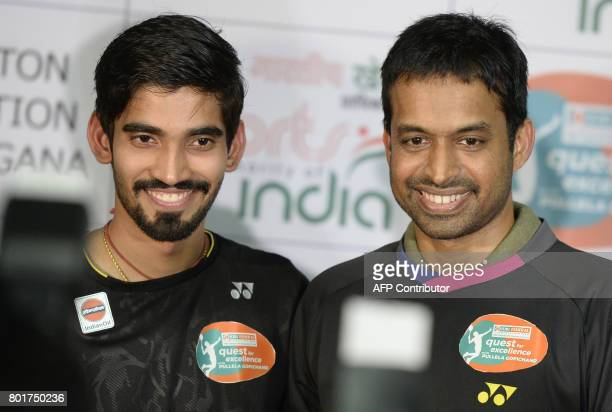 Indian badminton player Kidambi Srikanth and his coach P Gopichand pose for a photograph during a press conference in Hyderabad on June 27 2017...