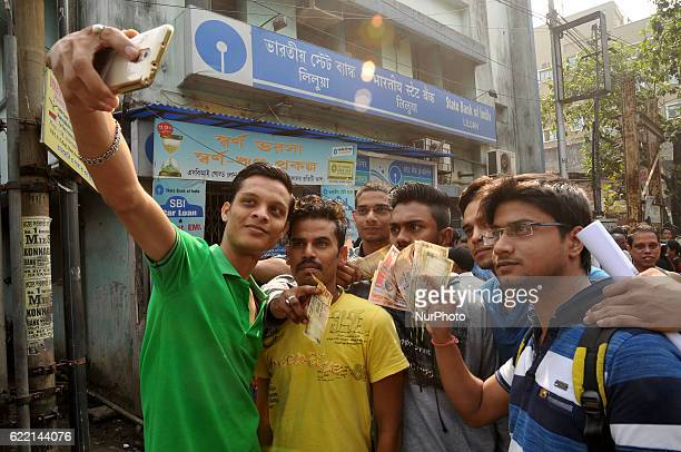 Indian bank customers Taken Pictures her mobile camera with old Indian Rupee 500 and 100 outside a bank prior to depositing and exchanging 500 and...