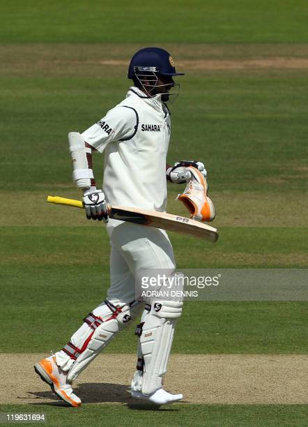 Indian batsman Abhinav Mukund carries his shoe as he runs down the wicket after losing his balance after playing a shot against England during day...