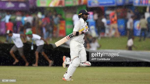 Indian batsman Abhinav Mukund leave the field as rain delays play during the third day of the first Test match between Sri Lanka and India at Galle...