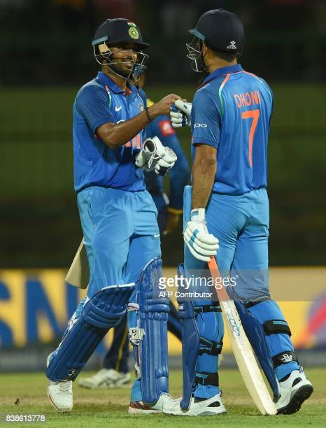 Indian batsman Bhuvneshwar Kumar celebrates with teammate Mahandra Singh Dhoni after victory in the second one day international cricket match...