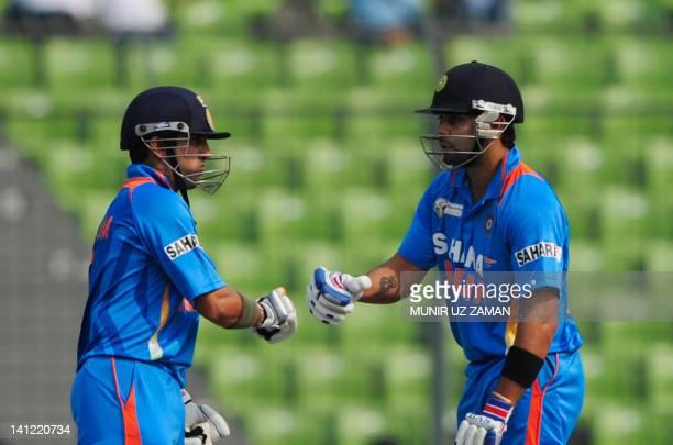 Indian batsman Gautam Gambhir congratulates teammate Virat Kholi for scoring a boundary during the one day international Asia Cup cricket match...