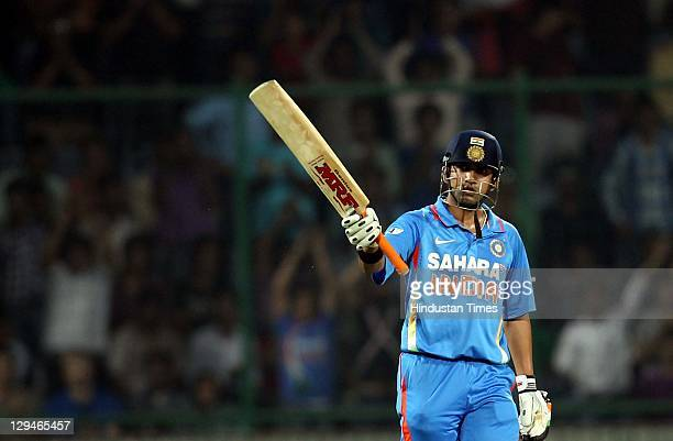 Indian batsman Gautam Gambhir raises his bat after completing his halfcentury during the 2nd One Day International cricket match between India and...