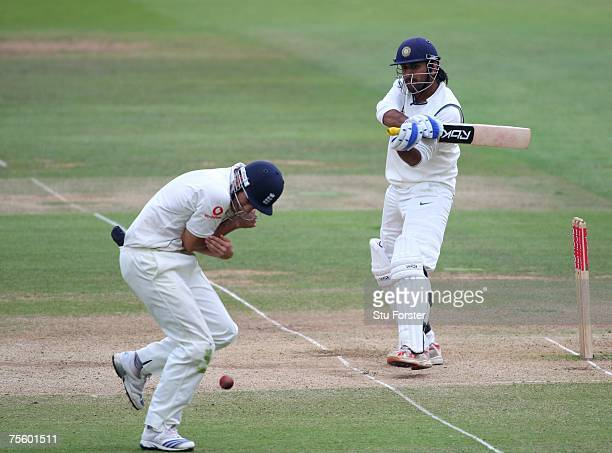 Indian batsman Mahendra Dhoni hits a boundary past fielder Alastair Cook during day five of the First Test Match between England and India at Lords...