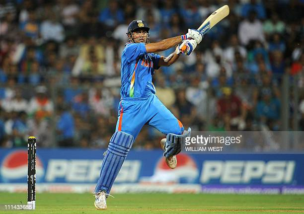 Indian batsman Mahendra Singh Dhoni hits a drive off the back foot from the Sri Lankan bowling during the ICC Cricket World Cup 2011 final played at...