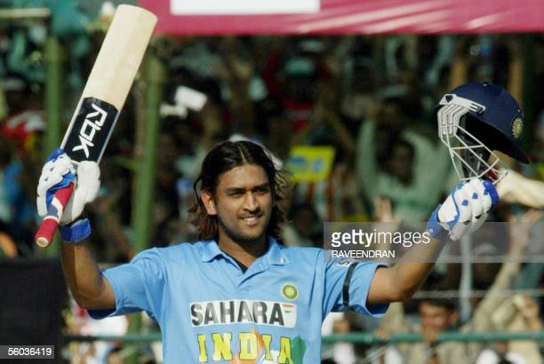 Indian batsman Mahendra Singh Dhoni waves his bat and helmet after he scored a century during the third oneday international match between India and...