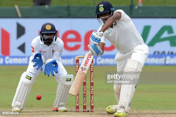 Indian batsman Ravichandran Ashwin plays a shot in front of Sri Lankan wicketkeeper Niroshan Dickwella during the second day of the second cricket...