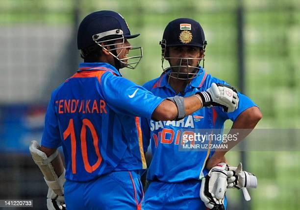 Indian batsman Sachin Tendulkar and teammate Gautam Gambhir look on as they wait for the third umpire decision during the one day international Asia...