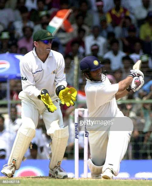Indian batsman Sachin Tendulkar hits a ball for six runs to reach a century as Australian wicketkeeper Adam Gilchrist looks on during the third day...