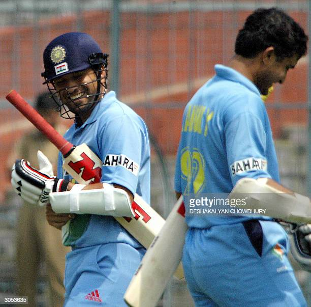 Indian batsman Sachin Tendulkar smiles as he passes by Indian captain Sourav Ganguly during a practice match on the second day of a conditioning camp...