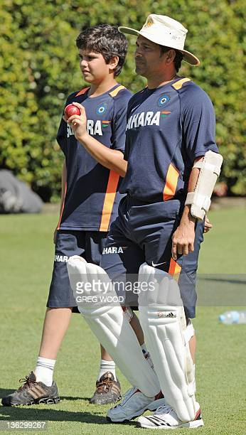 Indian batsman Sachin Tendulkar stands alongside his son Arjun as they watch a nets practice session at the Sydney Cricket Ground on January 1 2012...