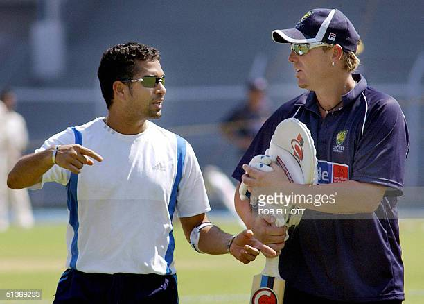 Indian batsman Sachin Tendulkar with his left arm taped because of tennis elbow gestures towards Australian spin bowler Shane Warne at a practice...