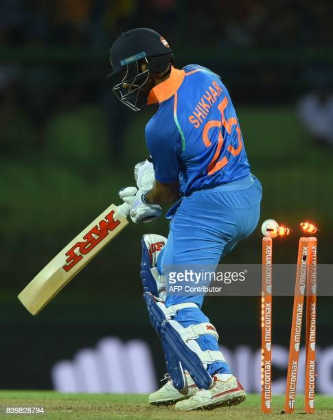 Indian batsman Shikar Dhawan is bowled out by Sri Lankan cricketer Lasith Malinga during the third one day international cricket match between Sri...