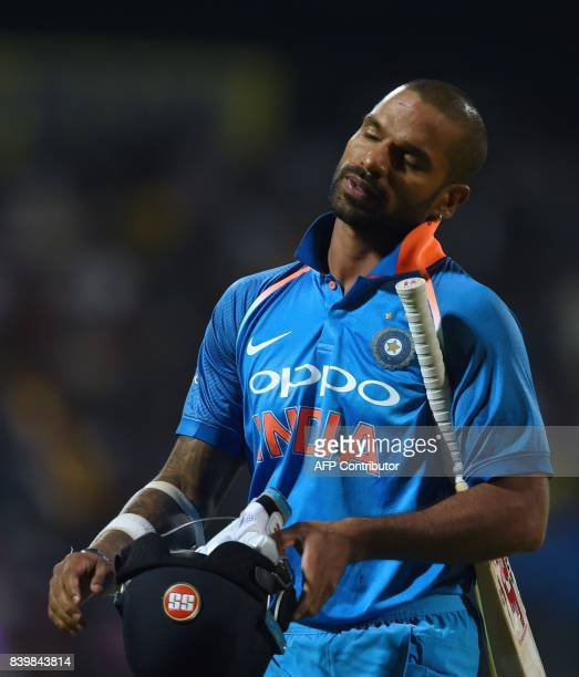 Indian batsman Shikar Dhawan leaves the pitch after being dismissed during the third one day international cricket match between Sri Lanka and India...