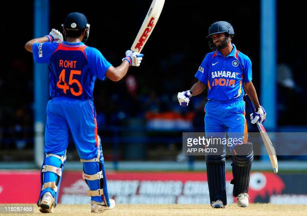 Indian batsman Shikhar Dhawan celebrates after scoring a half century with teammate Rohit Sharma during the first ODI between West Indies and India...