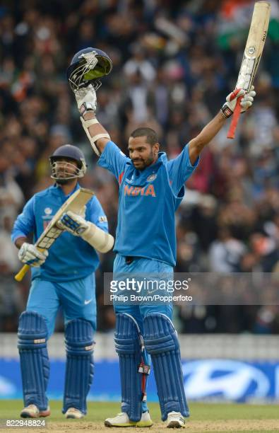 Indian batsman Shikhar Dhawan celebrates reaching his century during his innings of 102 not out applauded by teammate Dinesh Karthik in the ICC...
