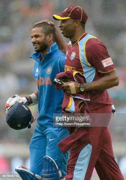 Indian batsman Shikhar Dhawan leaves the field with West Indies bowler Kieron Pollard during a rain delay in the ICC Champions Trophy group match...